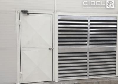 Puerta acústica y celosías louver en encierro acústico en sala de máquinas.